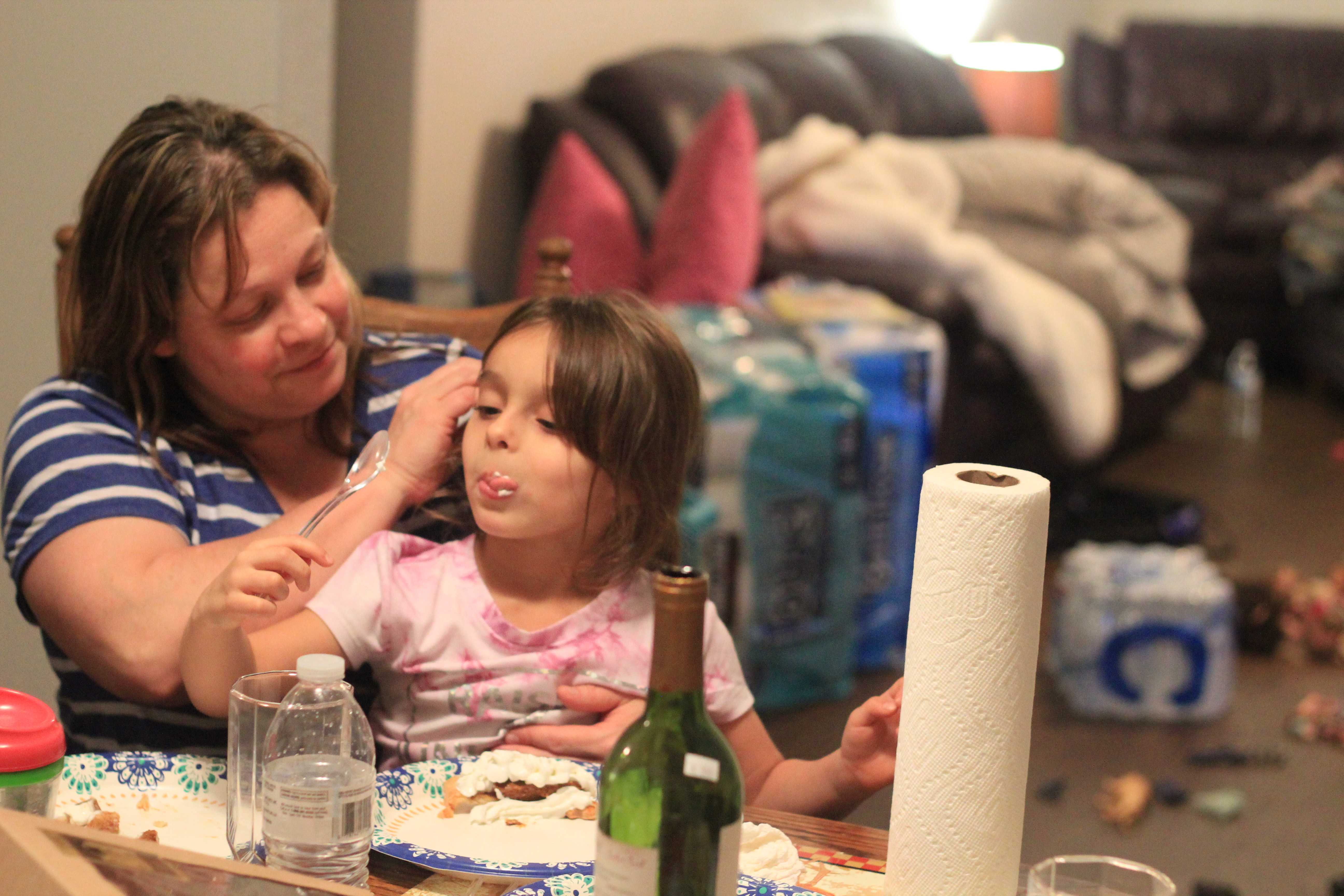 Elizabeth Marc, 42, Paradise wildfire survivor, feeds her daughter Isabelle, 4, spoonfuls of cottage cheese as the rest of her family eats dinner in their temporary rental home on Nov. 23 in Orland, Calif. The Marc family — Elizabeth, Isabelle, Paul, 50, and Francis, 17 — lost their home of two years when the most deadly fire in state history broke out on Nov. 8. (Lorenzo Morotti/Golden Gate Xpress)