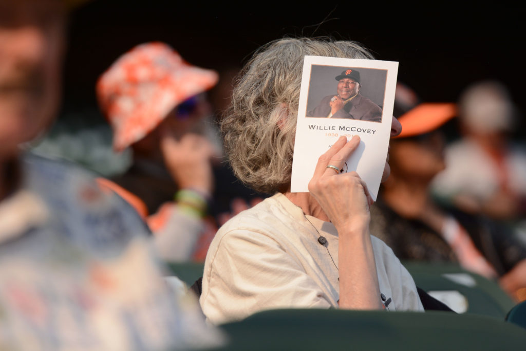 A San Francisco Giants fan shields her face from the sun with a program to at Willie McCovey's celebration of life at AT&T Park in San Francisco, Calif., on Thursday, Nov. 8, 2018. The former Giants hall of fame slugger,