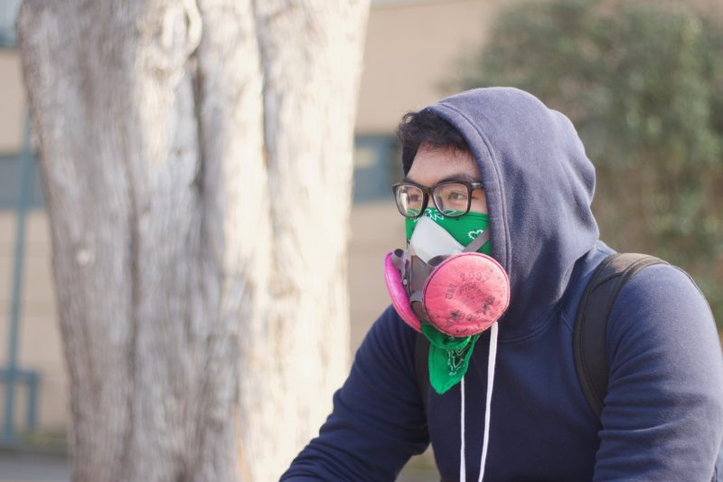 Malorn Jake Carlos, 18, political science major, wears a face mask because of the smoke caused by fires near Chico on campus at SF State on Friday November 9, 2018. © (Oscar Rendon/GoldenGateXpress)
