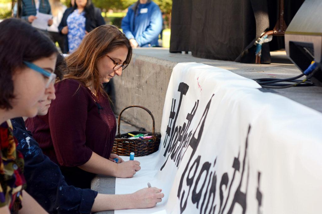 Emily Simmons, 24, a student experience architect for SF Hillel, writes a note to victims of the shooting at the Tree of Life synagogue in Pittsburgh, Pa., at a vigil held at Malcolm X Plaza in San Francisco, Calif. on Monday, Nov. 5, 2018. (Aaron Levy-Wolins/Golden Gate Xpress)
