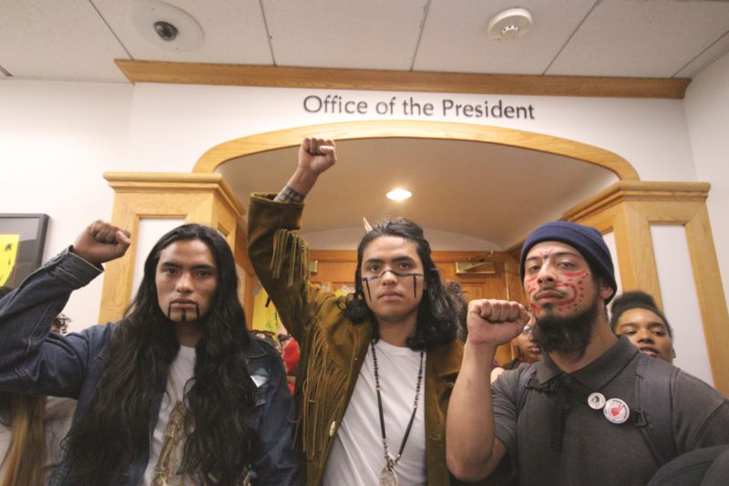 (L-R) Raphael Clark-Faust, Gabriel Clark-Faust, and Rogelio Martin stand in front of the president's office during a walkout in honor of the '68 strikers at SF State on Thursday November 8, 2018. © (Oscar Rendon/GoldenGateXpress)