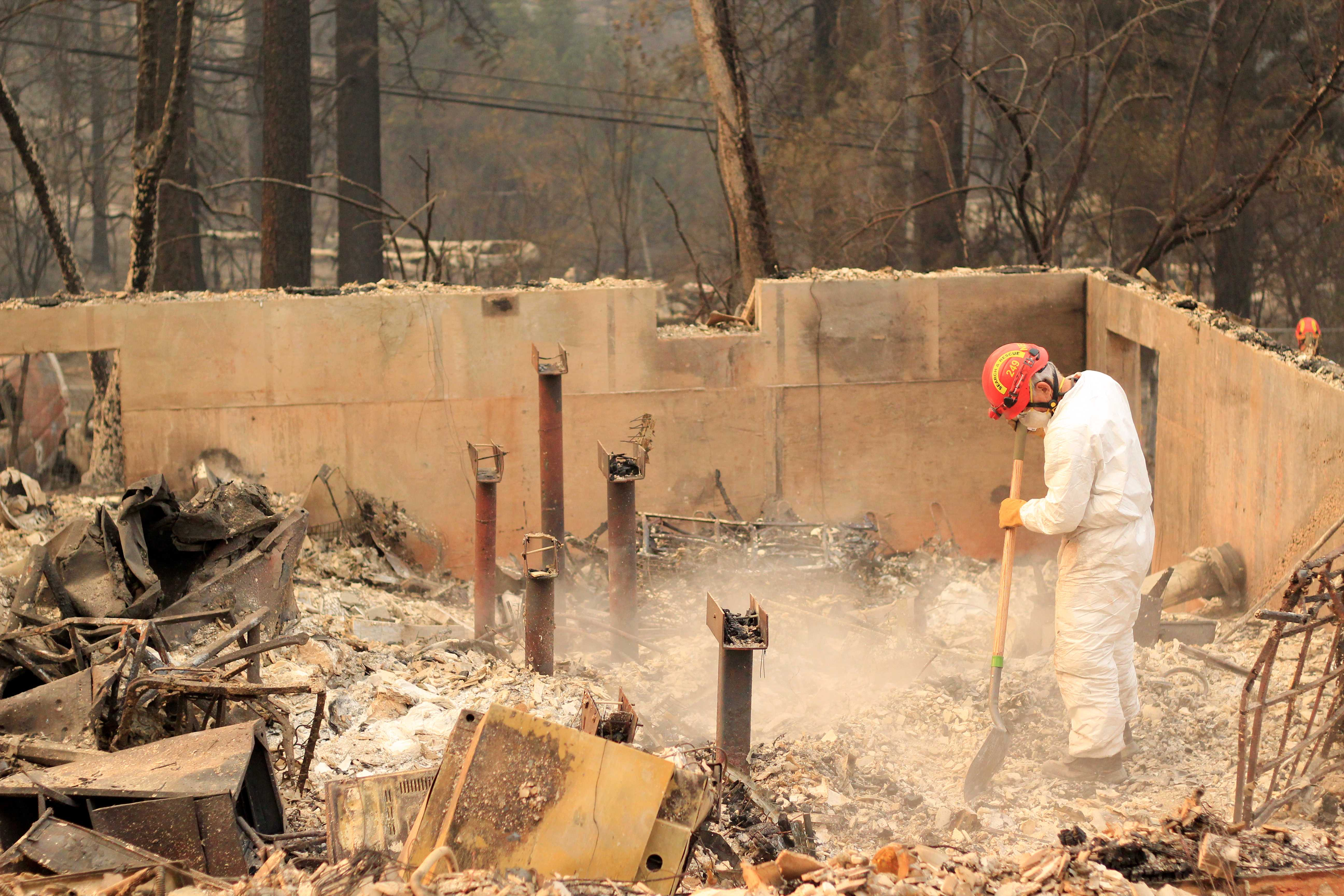 Santa Clara Sheriff's search and rescue volunteer digs through layers of burnt debris in the remnants of a house off New Skyway in Magalia, Calif., on Nov. 17, 2018. (Lorenzo Morotti/Golden Gate Xpress)