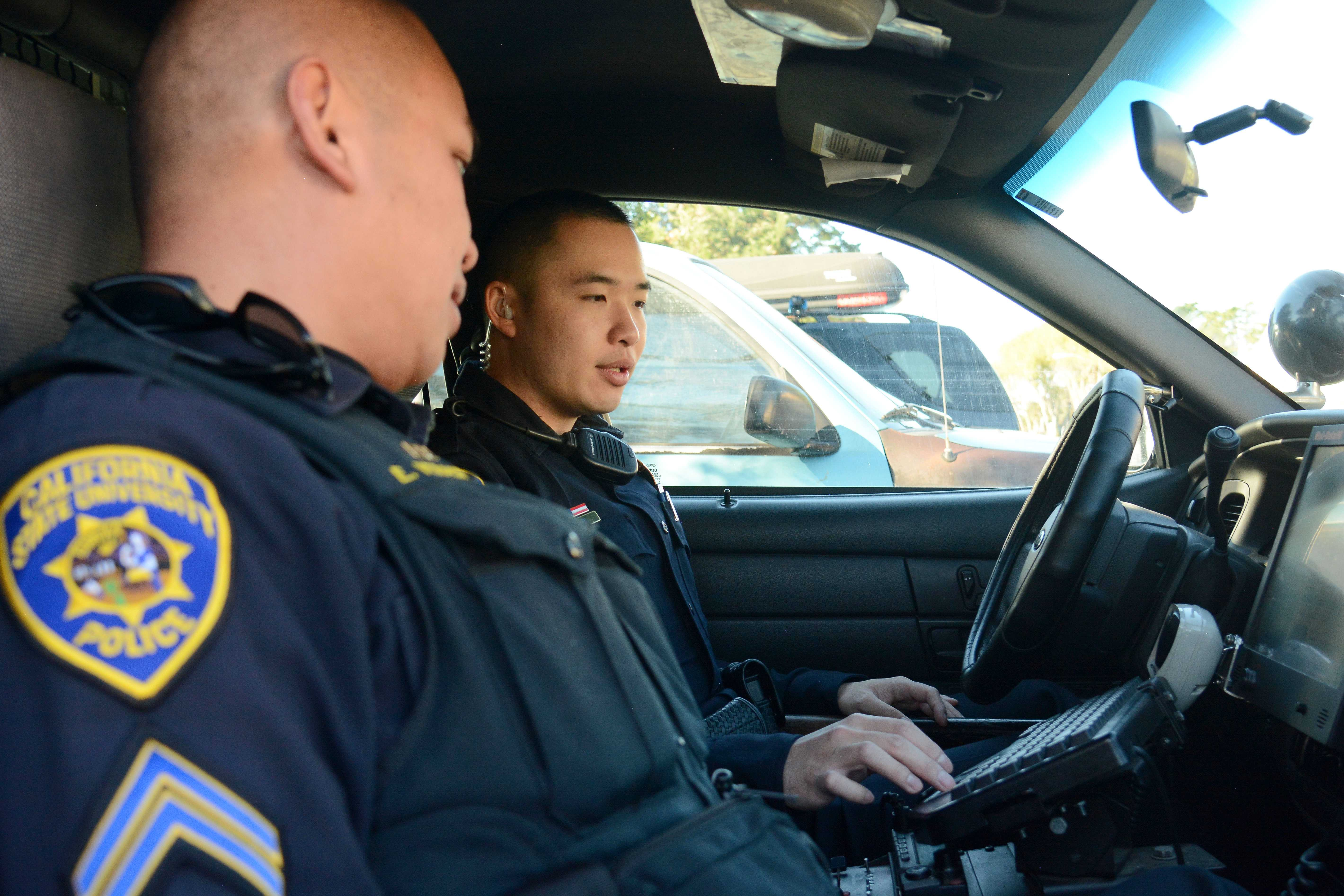 Cpl. Enrique Vera Cruz (left) chats with Officer David Lin (right) in a squad car by the University Police Department station at SF State in San Francisco, Calif., on Thursday, Dec. 6, 2018. Vera Cruz, a six-year veteran of the SF State's police force, is training Lin - who recently graduated from a police academy. (Aaron Levy-Wolins)