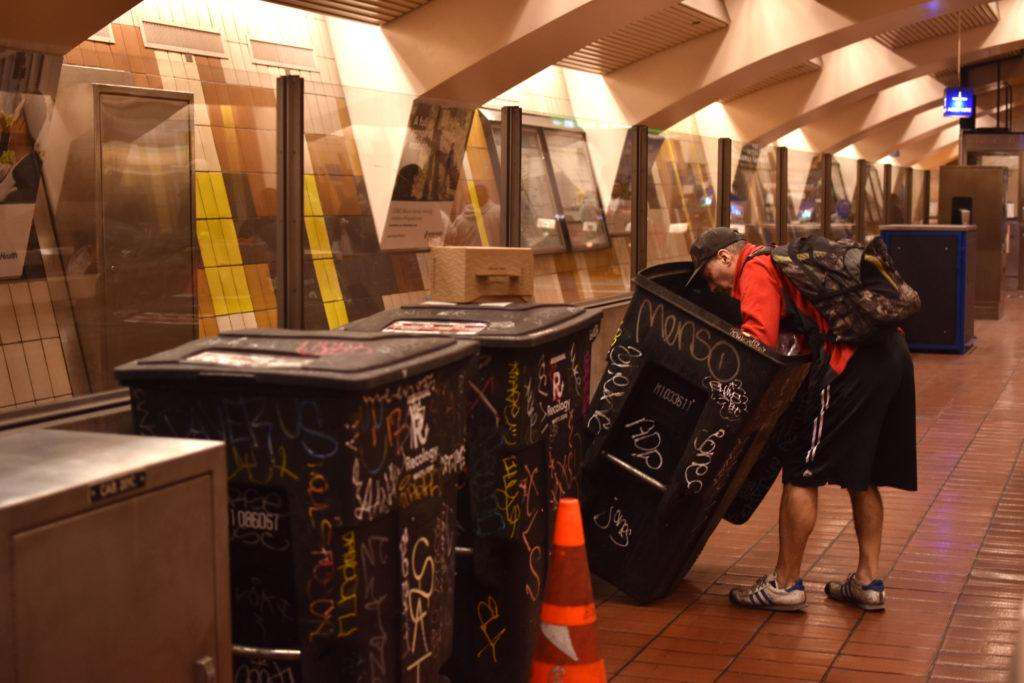A person rifles through a garbage bin at Mission Street BART subway station on Saturday, Jan. 26 in San Francisco.
