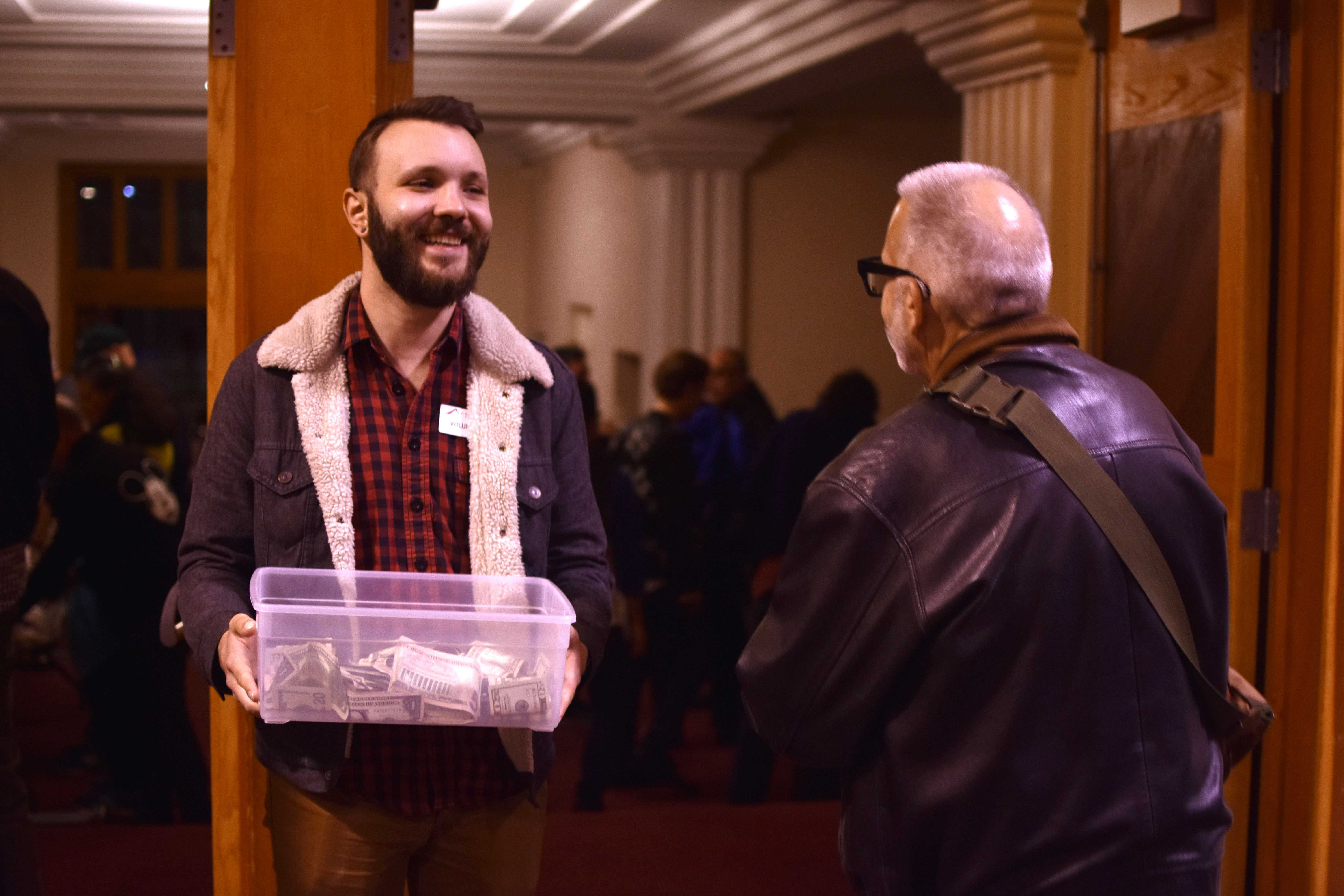 Mike Mykolaichuk collects money in a donation box as guests leave the benefit concert to fund Campfire disaster relief for Paradise at Bahá'í Center of San Francisco on Sunday, Jan. 27.