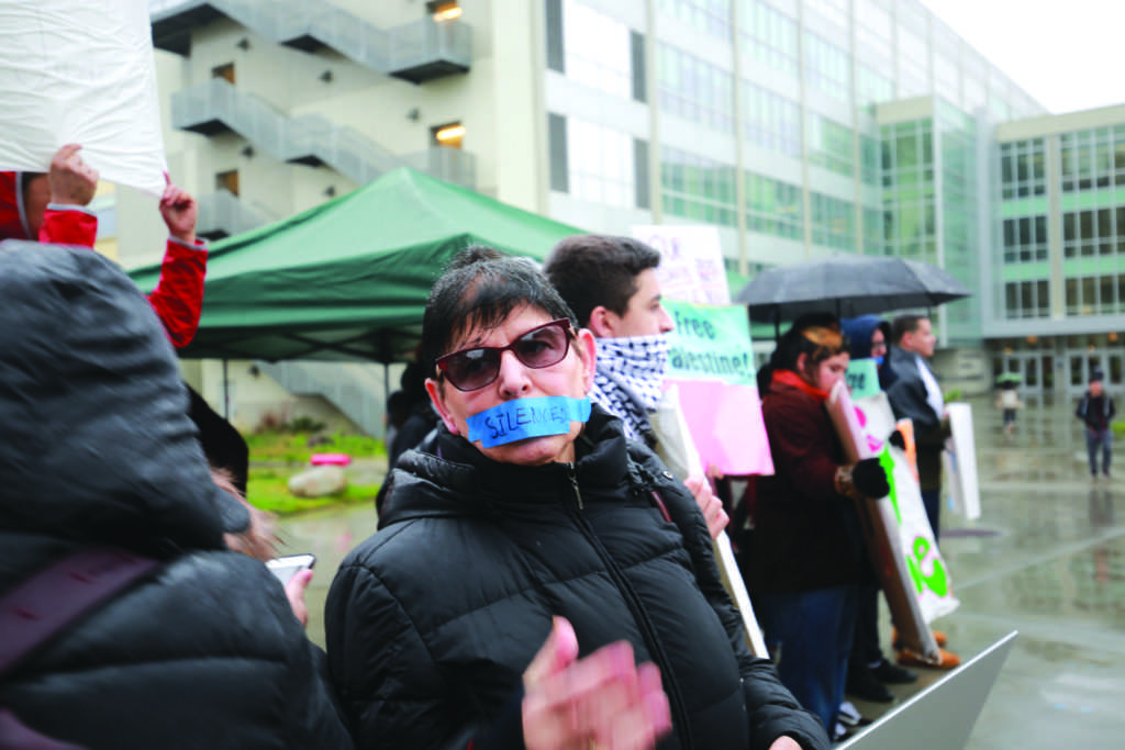 "Arab and Muslim Ethnicities and Diasporas studies profes- sor Rabab Abdulhadi has her mouth covered in tape labelled  ""SILENCED"" at a demonstration in the quad in front of the Administration Building at SF State on Feb. 13, 2019. JAMES CHAN/ Golden Gate Xpress"