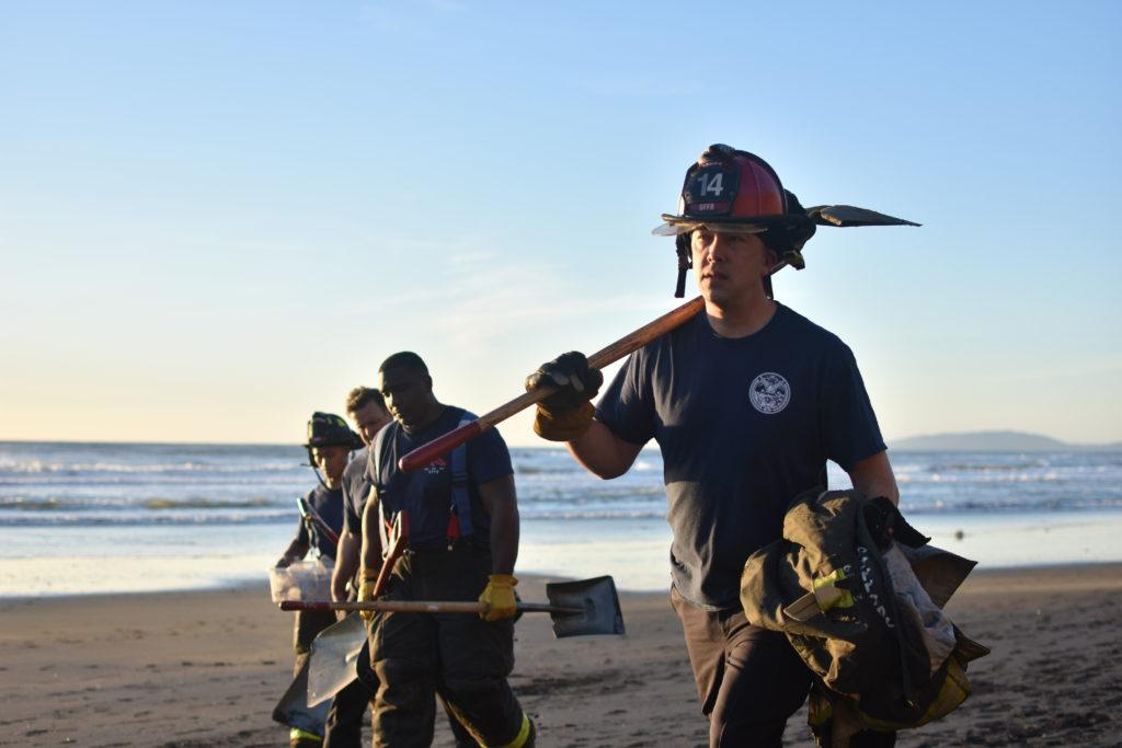 Local firefighters carry back shovels after a two hour attempt at rescuing a woman trapped in a mudslide at the coast of Fort Funston on Friday, Feb. 22, 2019.