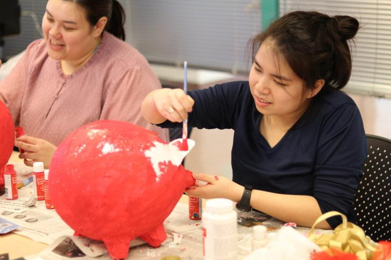 Mei Kelly, a Chinese flagship major, paints a papier-mache pig that's being used as a table center piece for the Chinese New Year Celebration in the humanities building on Feb. 20, 2019.