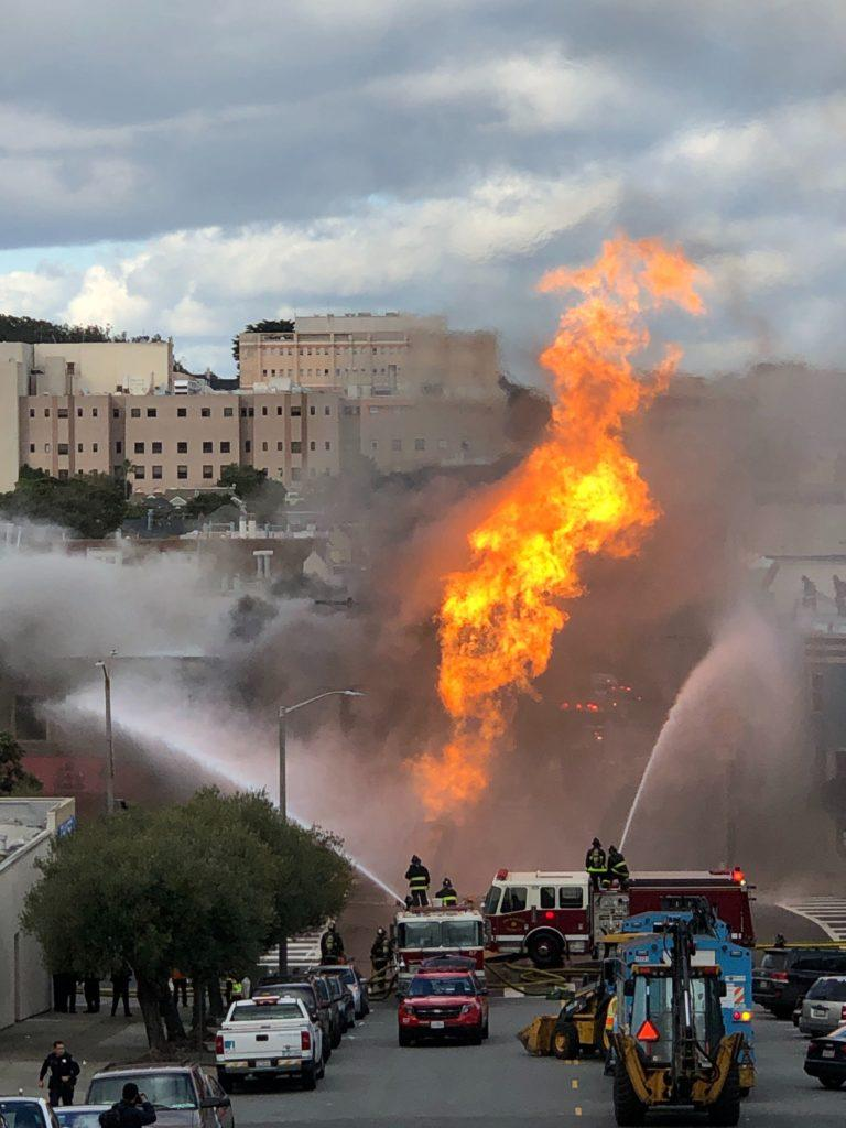 Firefighters spray water to contain the 3-alarm blaze on Parker Avenue and Geary Boulevard in San Francisco's Richmond District on Feb. 6, 2019. (Chris Robledo/ Golden Gate Xpress)