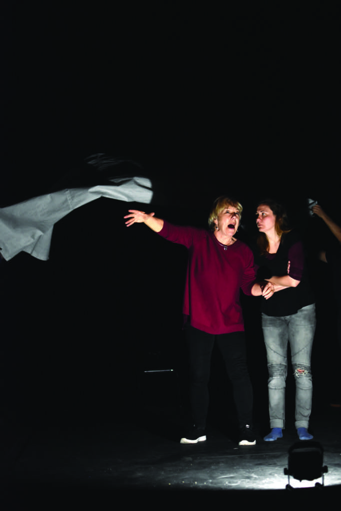 AFTLS actors Tricia Kelly (left) and Ffion Jolly (right) perform a stormy scene as Jon Dryden Taylor and Fred Lancaster lift and drop a tarp for effect behind them during a rehearsal for King Lear at SF State Little Theatre on March 9, 2019. (Lola Chase/ Golden Gate Xpress)