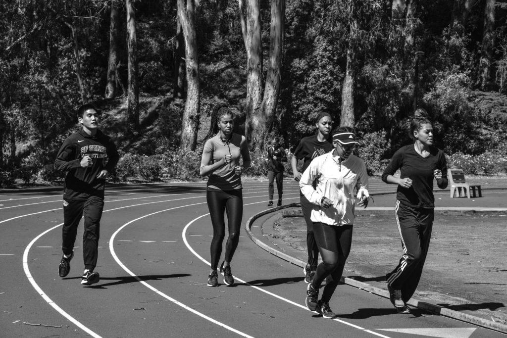 Senior Jacob Mendoza (left) runs around the track during practice on March 15. He is a part of the SF State wrestling team and the track team as well. Mendoza joined the team to help meet the 18-person requirement for the spring 2019 semester. (SHAYLYN MARTOS/Golden Gate Xpress)
