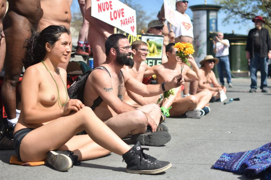 Inti Gonzales (left), daughter of parade organizer Gypsy Taub, sits on the pavement with fellow nudists for the Nude Love Parade at Jane Warner Plaza in the Castro on St. Patrick's Day, March 17, 2019.