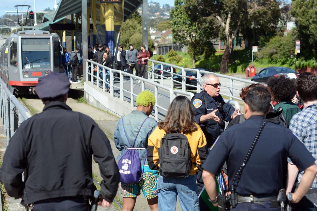 San Francisco Police officers stand guard as students protest the CSU settling a lawsuit regarding anti-Zionism by blocking Muni tracks at 19th and Holloway Avenues on Thursday, Mar. 21, 2019. (AARON LEVY-WOLINS/ Special to Golden Gate Xpress.)