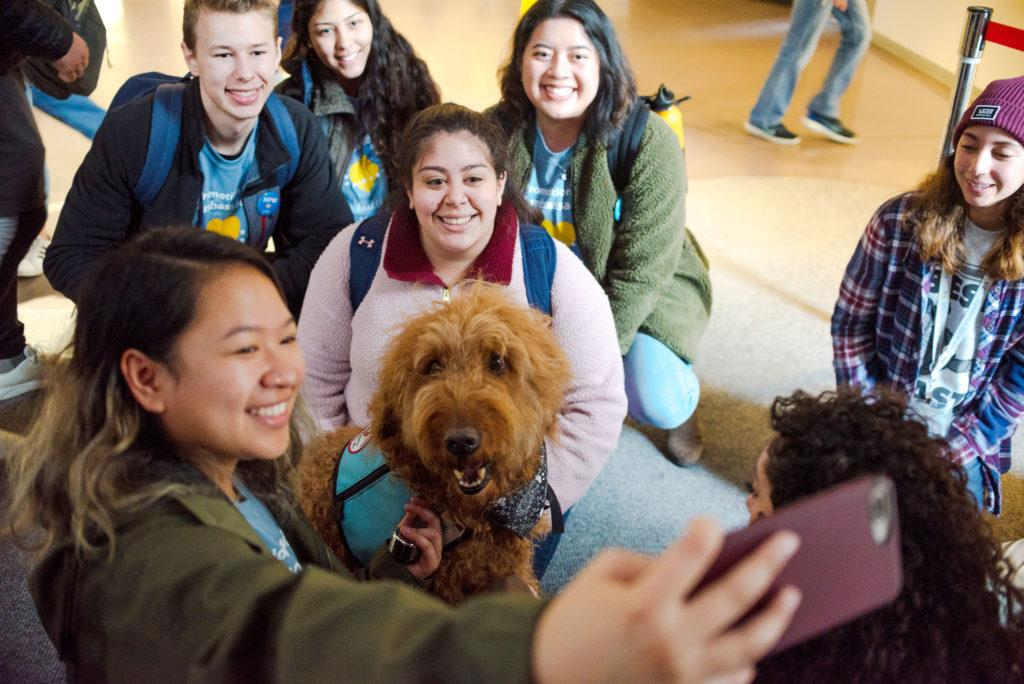 BECA major Jalyn Ocampo (front-left), biology-physiology major Luke Wesley (upper-left), biology major Jessica Bermudez (upper-center), health education major Samantha Hudson (center), and health education major Rizalyn Hiyao (upper-right) pose for a photo with SPCA Wag Brigade therapy dog Toby on Tuesday, March 5, 2019. Toby was one of four dogs that visited the Cesar Chavez Center as part of the school's Therapy Animal program.