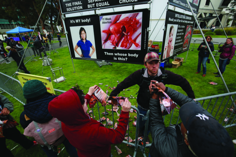 Matthew Vaughn argues with students as they tear up pamphlets during a demonstration in the quad by the organizations Project Truth, Genocide Awareness Project and Center for Bioethical Reform on  April 15, 2019. Vaughn first identified himself as John Newton. (JAMES CHAN/ Golden Gate Xpress)