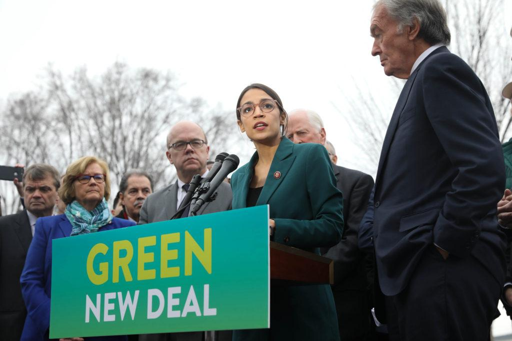 Representative Alexandria Ocasio-Cortez (center) speaks on the Green New Deal with Senator Ed Markey (right) in front of the Capitol Building in February 2019. (Photo by 'Senate Democrats' via Wikimedia Commons.)