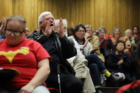 San Francisco senior resident Doug Buckwald cheers on a public commenter protesting class cancellations at City College of San Francisco
