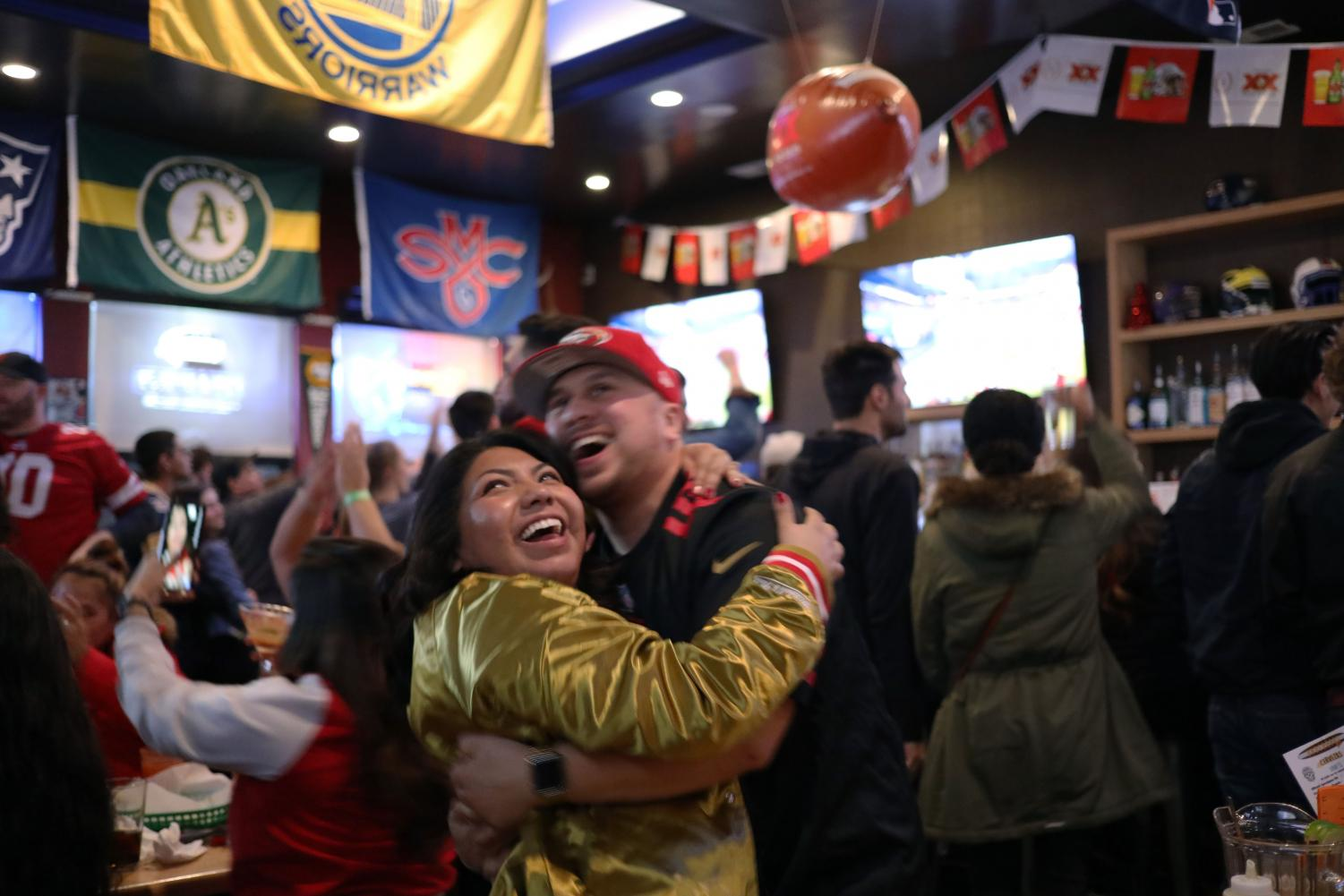 Karen Bueno Manny Ramirez embrace in a hug after the San Francisco 49rs score a touchdown in the second half of Super Bowl LIV at Underdogs Too in San Francisco Calif., on Sunday February 2, 2020. (Emily Curiel)