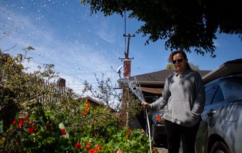 Janelle October waters her plants in her front yard in Pomona, California. (Maddison October / Golden Gate Xpress)