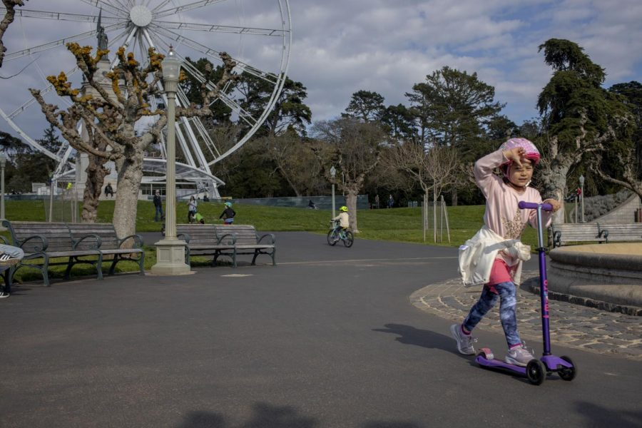 A child rides their scooter around a fountain at Golden Gate Park in San Francisco on March, 19, 2020 (Emily Curiel / Golden Gate Xpress).