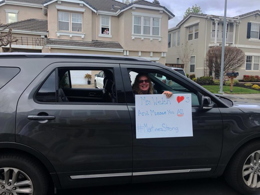 Tammi Welch, a teacher at Morello Park Elementary, poses for a photo with a sign during the parade of teachers in  cars that connected the community and the teachers from afar during the shelter in place. (Catherine Stites / Golden Gate Xpress)