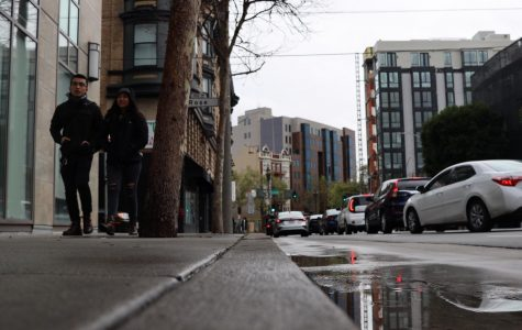 People walk on the sidewalk  towards a cat cafe  on a rainy day in Sam Francisco on Saturday March 14, 2020. (Emily Curiel / Golden Gate Xpress