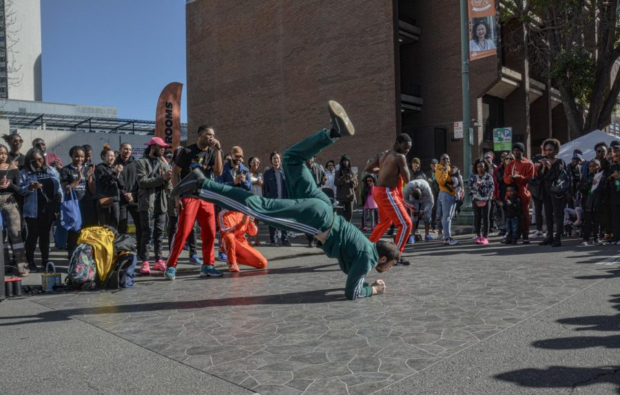 Oakland Originalz breaker and SF State student Tadhg Rush slides across the group's mat on his forearms during the Black Joy Parade in Oakland. Rush studies kinesiology at SF State. (Photo by shaylyn martos / Golden Gate Xpress)