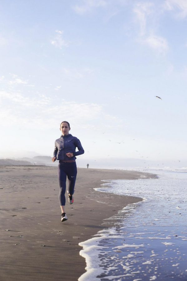 Shannon Rowbury, a three time Olympian, two time bronze medalist, American and World record holder, Nike Pro Runner and mom runs along the water at Ocean Beach. (Kameron Hall /Golden Gate Xpress)