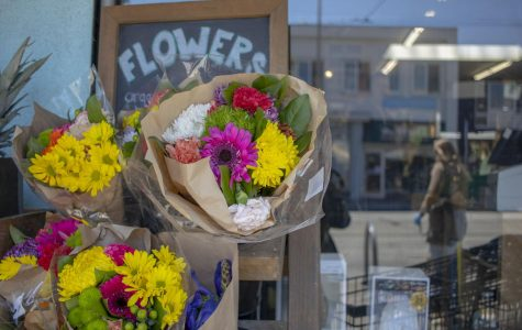 Flowers are displayed outside of a grocery store as a person with medical gloves walks by in the Sunset District in San Francisco, California. (Emily Curiel / Golden Gate Xpress)