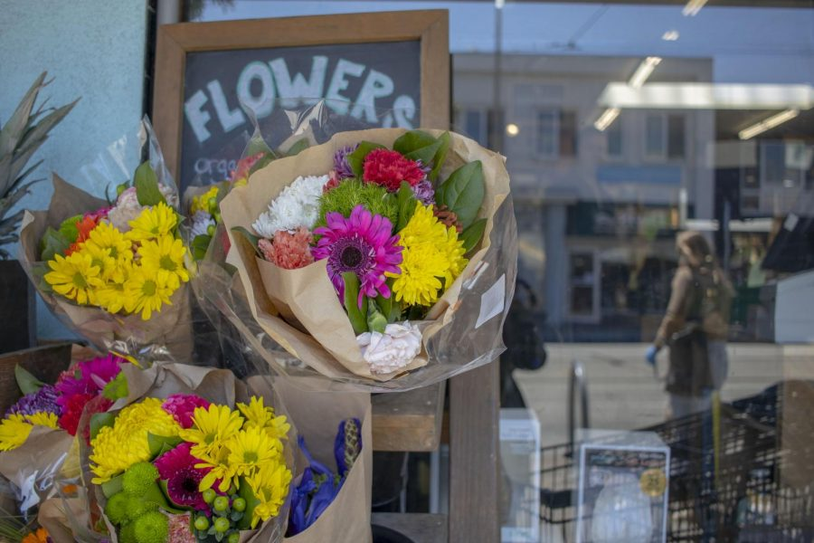 Flowers+are+displayed+outside+of+a+grocery+store+as+a+person+with+medical+gloves+walks+by+in+the+Sunset+District+in+San+Francisco%2C+California.+%28Emily+Curiel+%2F+Golden+Gate+Xpress%29