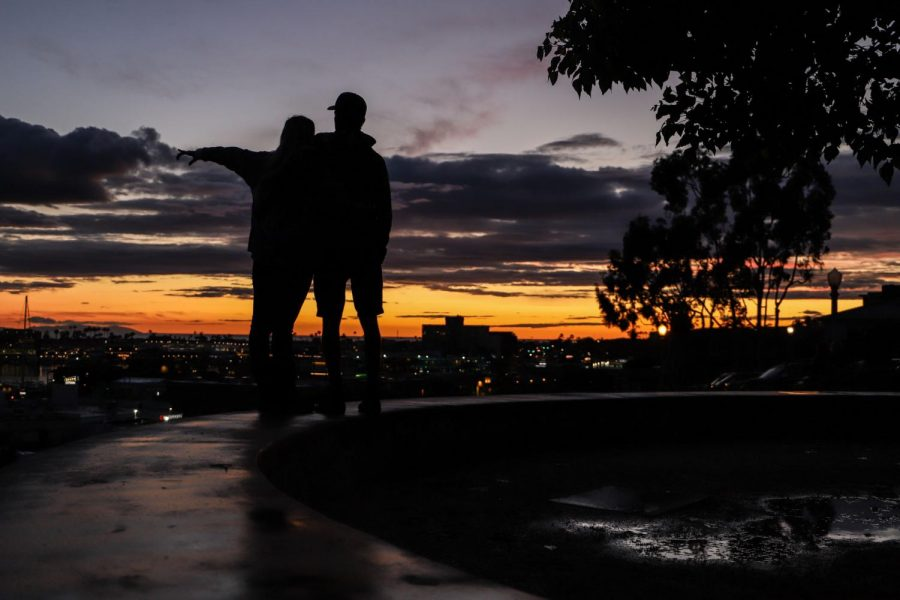 A couple watches the sunset at John Wayne Park in Newport Beach, Calif., on Friday, April 10, 2020. (Saylor Nedelman / Golden Gate Xpress)