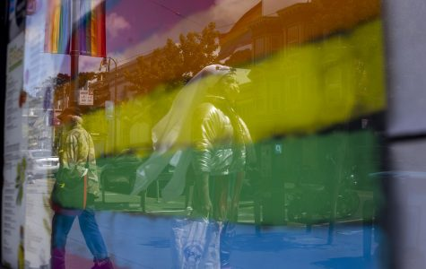 People walk pass a rainbow drawing taped to a restaurant window on Castro Street in San Francisco California. (Emily Curiel / Golden Gate Xpress)