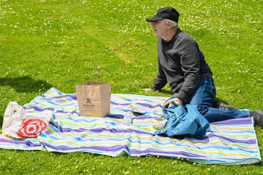 Geoffrey Martin waits for his partner at Golden Gate Park with the picnic he set up. (James Wyatt / Golden Gate Xpress)