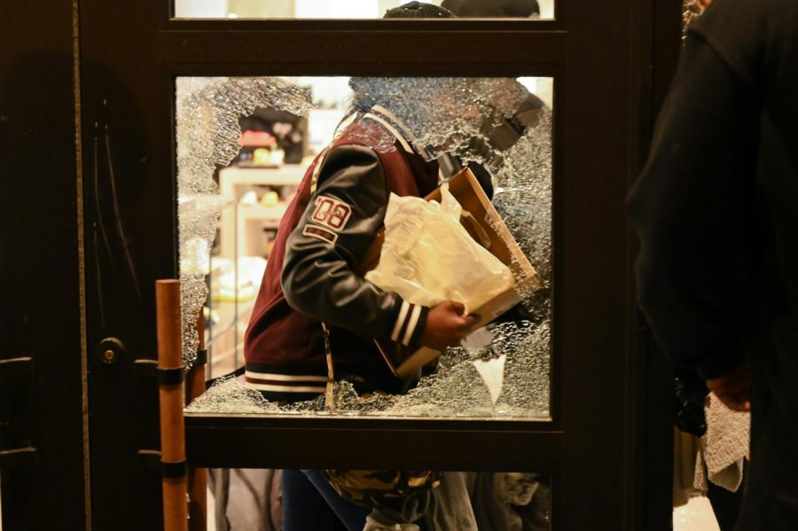 A man holds on to shoes after entering the UGG store located on Powell street, which was broken into Saturday, May 30, 2020 in San Francisco, Calif. Widespread vandalizing occurred throughout the city following the death of George Floyd, a detained and handcuffed black man in police custody in Minneapolis. (James Wyatt / Golden Gate Xpress)