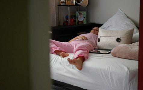 Lucy Da Silveira rests on her bed after a long shift working at Kaiser Permanente, in San Jose, California. (Daniel Da Silveira / Golden Gate Xpress)