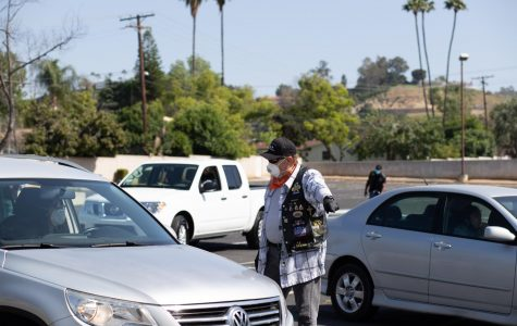 The Sabbath Keepers guide cars through the parking lot to the food drive. Photographed in Riverside, California. (Maddison October / Golden Gate Xpress)