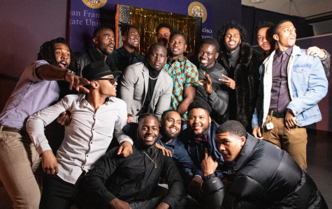 A group gathers in front of the photo booth to take a photo at the Black Men's Appreciation event in the Annex on February 27, 2020.