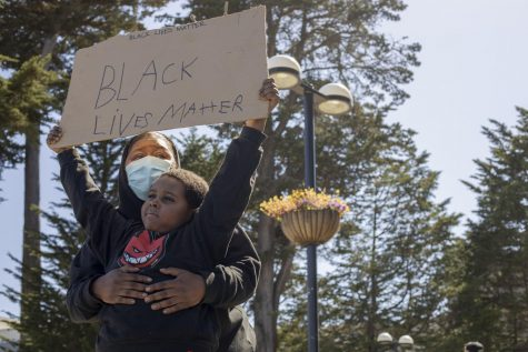 "Jace Smith holds up a sign that says, ""BLACK LIVES MATTER,"" while his mother, Veronica Smith, holds him during a peaceful protest against police brutality and systemic racism in front of SF State at 19th and Holloway on Sunday, June 7, 2020. (Emily Curiel / Golden Gate Xpress)"