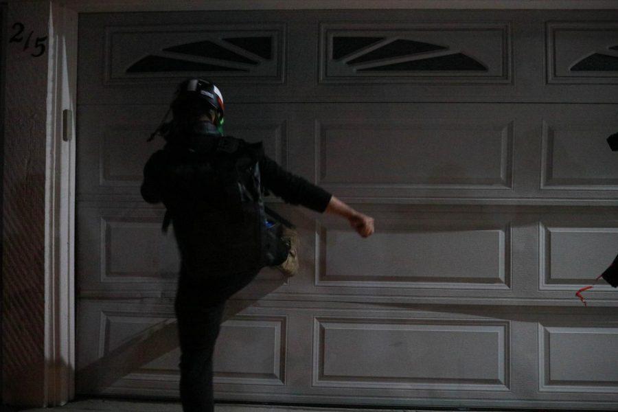 A protester kicks the garage door at the residence of Walnut Creek's Mayor, during the twilight protest in Walnut Creek, Calif., on Jun. 17, 2020 (Harika Maddala / Golden Gate Xpress)