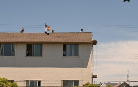 People protest from a house along the Great Highway June 2, 2020in San Francisco, Calif. The protest was in response to the death of George Floyd, a detained and handcuffed Black man in police custody in Minneapolis. (James Wyatt / Golden Gate Xpress)
