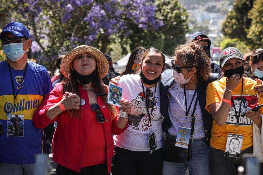 Laura Monterrosa, madre de Sean, muestra su retrato y ve a La Dona cantar durante el Día de Tucan, un evento público realizado en honor a Sean Monterrosa, cerca de Holly Park, en San Francisco, California, el 12 de junio de 2020. La Dona actuó la canción