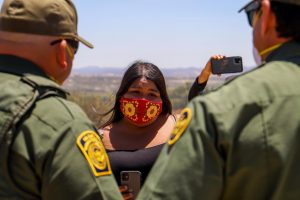 Cynthia Parada, a council woman of the La Posta band of the Kumeyaay tribe, explains to border patrol why it would be disrespectful to break up the group amidst their prayer. The protestors have taken to filming the action of USBP all day long, and at every interaction, to share on their social media sites and to ensure accountability. (Camille Cohen/ Golden Gate Xpress)
