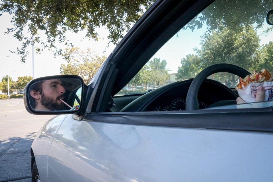 Will Dunton eats lunch while sitting in his car parked in shade in the parking lot outside In-N-Out Burger. Dunton, who is currently unemployed, spends his time walking at the City Park or hanging out with his friends. He plans to find a job in San Francisco and move back into the city. (Harika Maddala/ Golden Gate Xpress/ Brentwood, Calif., July 22, 2020)