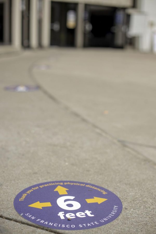 Signage taped on the ground at Malcolm X Plaza serves as a reminder for people to keep a six-feet distance.