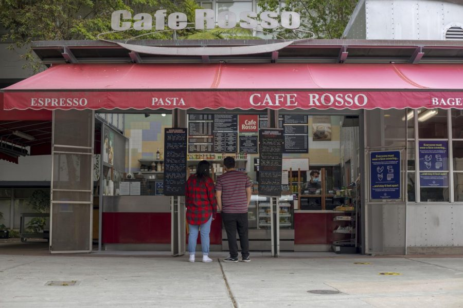 Two people look at a menu at Cafe Rosso as an employee waits to take their order behind a plexiglass barricade.