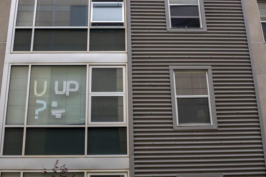 """Post-itnotes that say, """"U up?"""",are displayed on a dorm room window across from the Humanities building.The noteshave not been taken down since the Spring 2020 semester."""