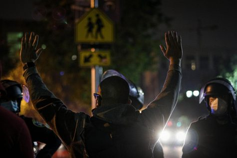 """A protester raises his hands up in surrender while standing in front of the police, following the arrest of a protester. """"I asked you all to fill up the gaps,"""" another protester said to the crowd in response to the arrest. They said that the police fired tear gas and pulled out a protester and handcuffed them during the chaos. (Golden Gate Xpress/ Oakland, CA, Aug. 28, 2020"""