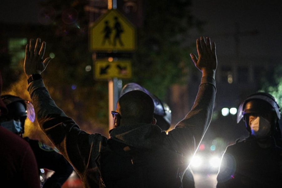 A protester raises his hands up in surrender while standing in front of the police, following the arrest of a protester.