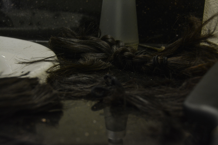 First, martos braided her long hair in three sections, which her father cut off with scissors. Before shaving her head, martos' hair was about 18 inches long, reaching down her back.