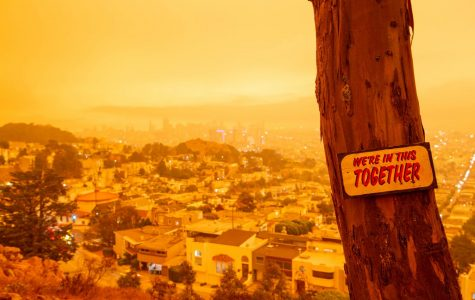 "A sign with the words ""We're in this together"" stands in front of an orange covered city view from Tank Hill (Golden Gate Xpress San Francisco, CA., Sept. 9, 2020)"